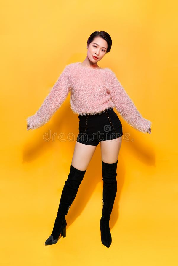 Short-haired girl in fashionable dancing. Young playful female model in stylish fur outfit. Beautiful happy woman having fun dance royalty free stock photography