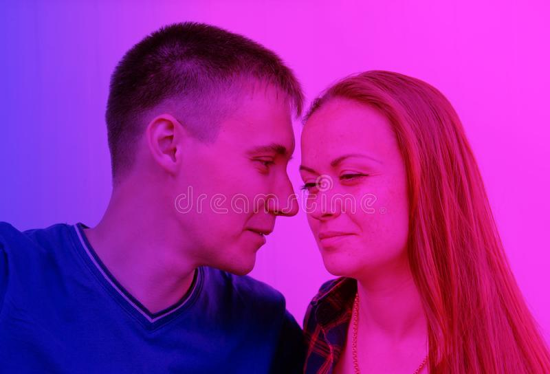 Short-haired guy in a T-shirt and girl with dark long hair in a shirt. pink and purple neon style.  stock photo