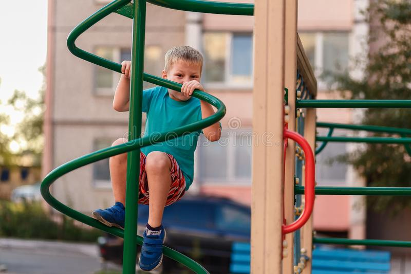 Short-haired seven-year-old boy climbs on the Playground near the house in the summer stock photography