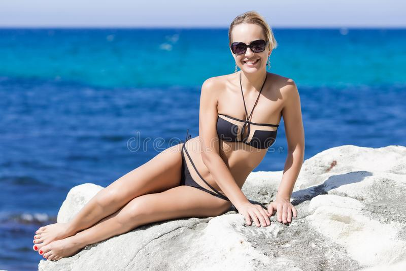 Short-haired tanned blond woman reclining on rock stock image