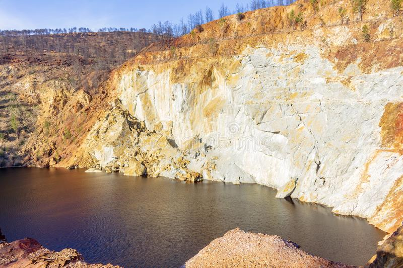 Short of the Peña del Hierro mine. View of the Peña del Hierro mine that remains covered with water of red color in Riotinto, Andalusia, Spain stock photography
