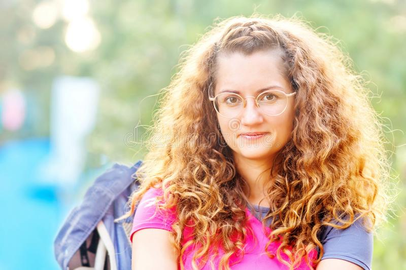 Young beautiful woman in glasses on the nature. Short-sighted young beautiful woman with curly hair wearing glasses on nature stock image