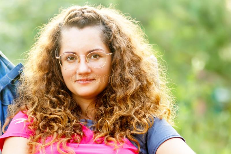 Short-sighted young beautiful woman in glasses on nature. Short-sighted young beautiful woman with curly hair wearing glasses on nature royalty free stock photography