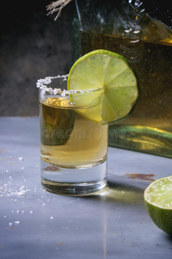 Short of tequila. Anejo with lime and salt over gray metal table royalty free stock image
