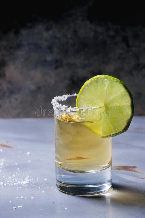 Short of tequila. Anejo with lime and salt over gray metal table stock photography