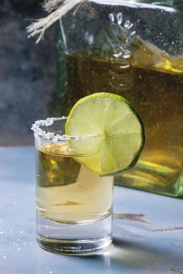 Short of tequila. Anejo with lime and salt over gray metal table stock image