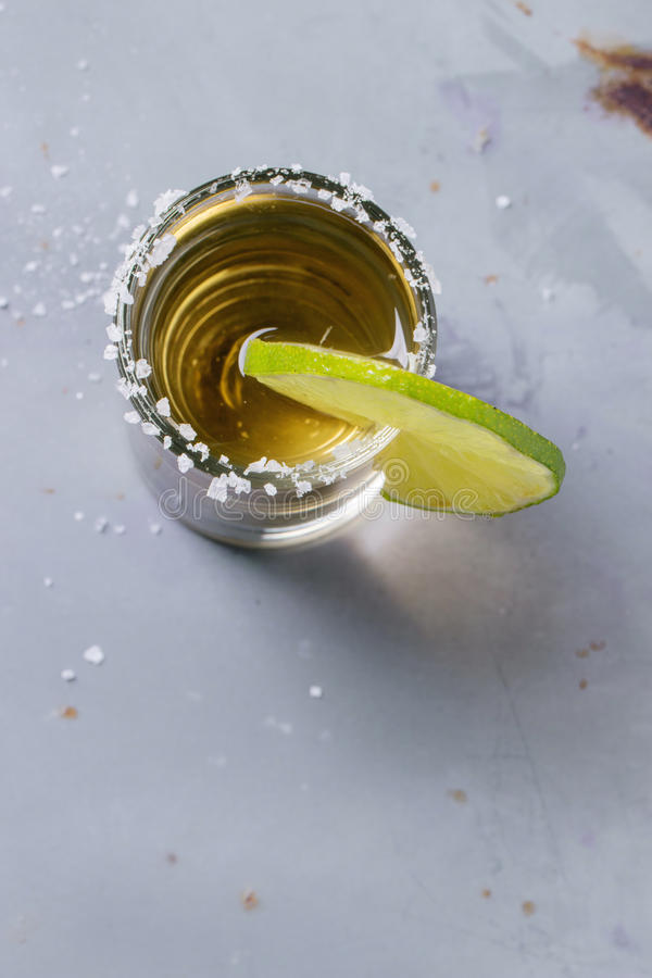 Short of tequila. Anejo with lime and salt over gray metal table. Overhead view royalty free stock photo