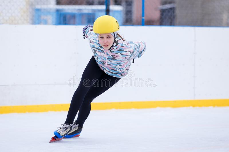 Speed skating young girl on training rink. Short track sportswoman. Speed skating young girl on training rink stock photography
