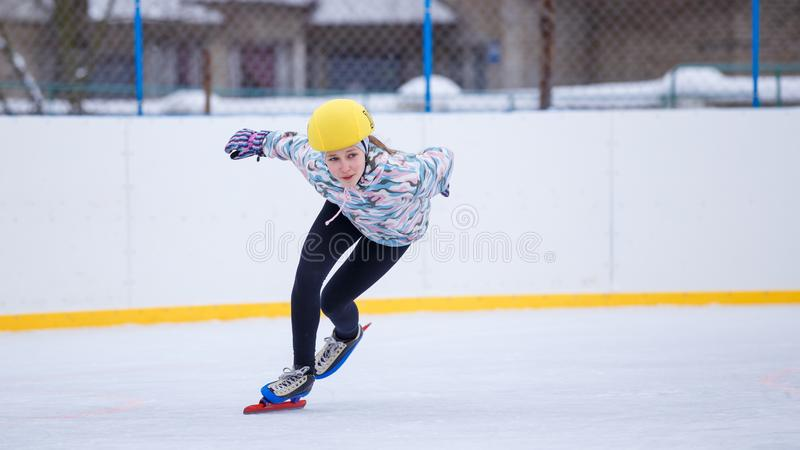 Speed skating young girl on training rink. Short track sportswoman. Speed skating young girl on training rink royalty free stock images
