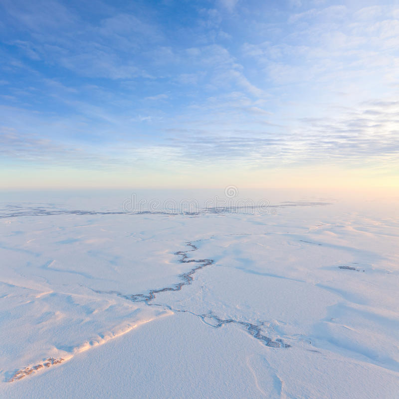 Short winter day above frozen tundra, top view. Aerial view above the endless snow covered tundra in time of short winter day stock images