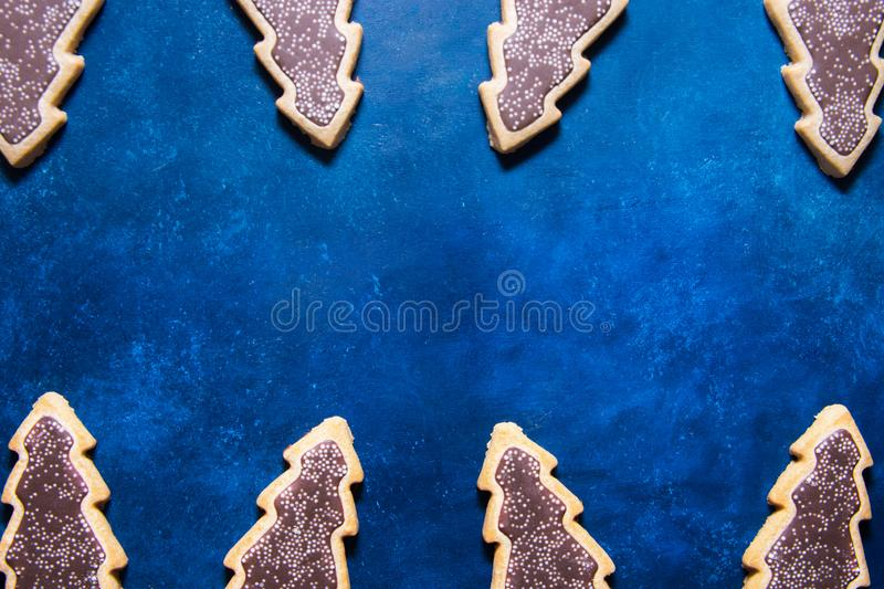 Shortbread cookies covered with chocolate icing in shape of Christmas tree on dark blue background. Creative holiday festive stock photo
