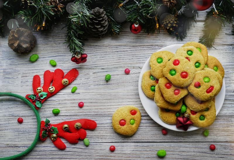 Shortbread cookies with multi colored candy and chocolate chips, served with glass of milk, square format.  royalty free stock photo