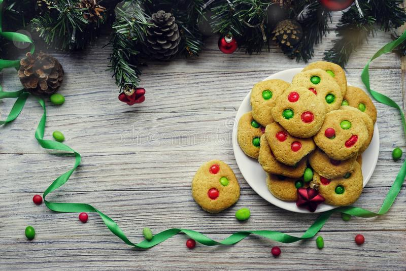 Shortbread cookies with multi colored candy and chocolate chips, served with glass of milk, square format.  royalty free stock images