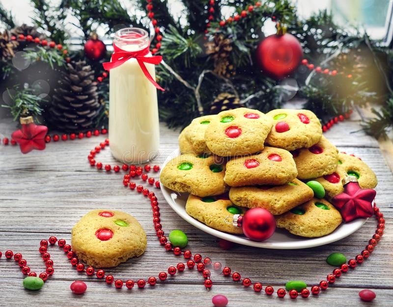 Shortbread cookies with multi colored candy and chocolate chips, served with glass of milk, square format.  stock photography