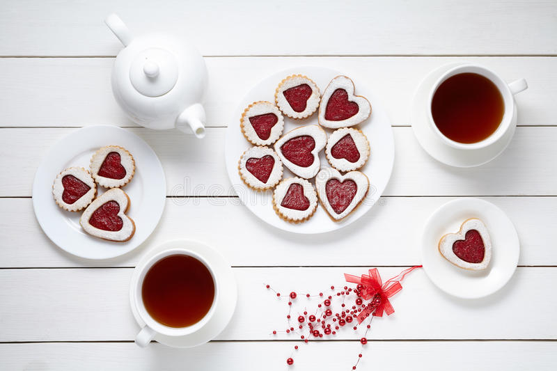 Shortbread heart shaped cookies for Valentines day with teapot and two cups of tea on white wooden background. Baked royalty free stock image