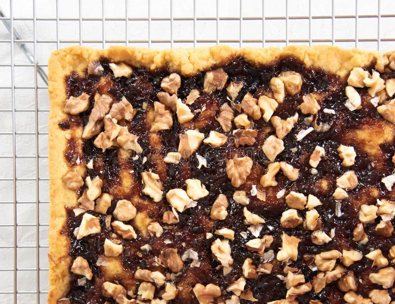 Shortbread pie with jam and walnuts on cooling rack stock image