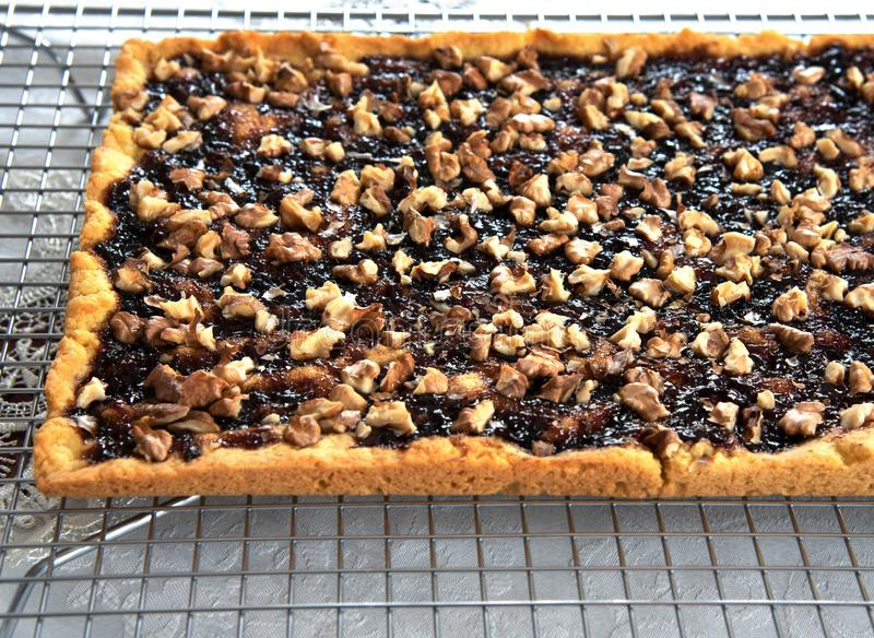 Shortbread pie with jam and walnuts on cooling rack royalty free stock photography