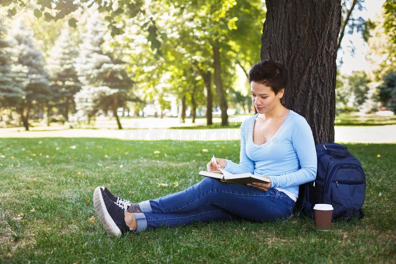 Shorthaired woman reading a book outdoors stock photos