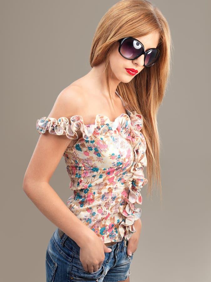 Shorts das calças de brim dos óculos de sol da mulher da forma foto de stock royalty free