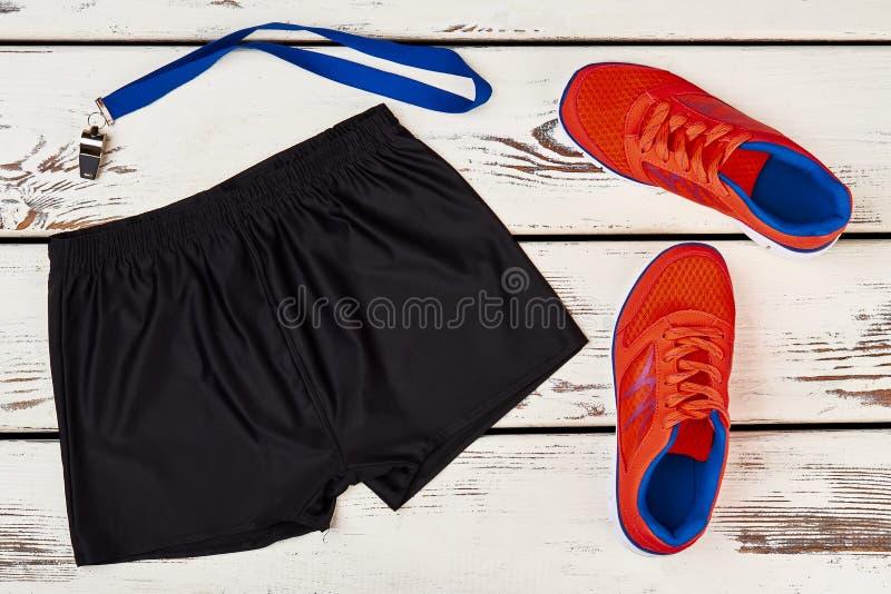 Shorts noirs, espadrilles oranges, sifflement photo libre de droits