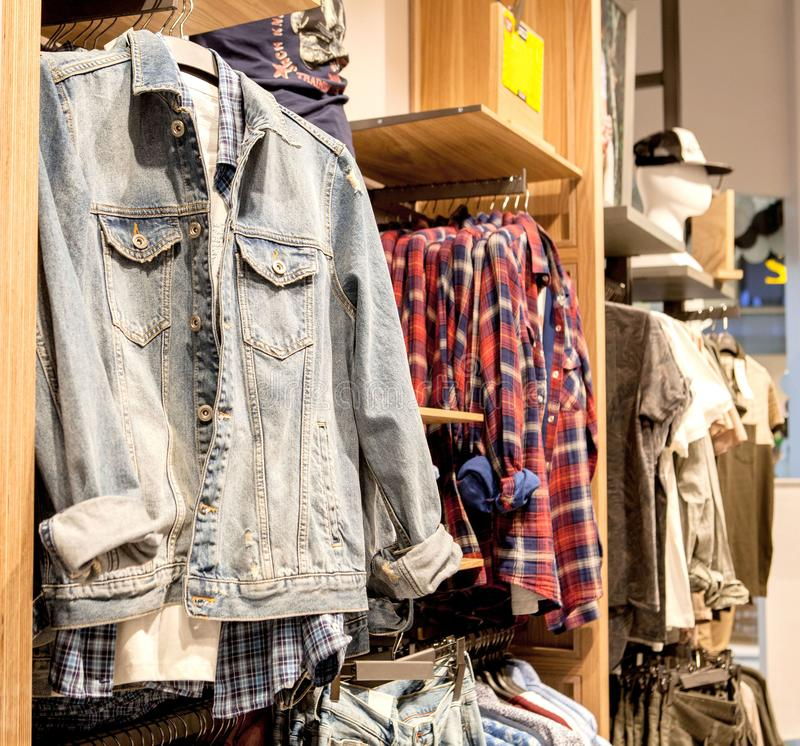 Shorts,shirts, T-shirts and jacket on the store shelf. Fashionable clothes on the shelves in the store. Showcase, sale, shopping. stock photography