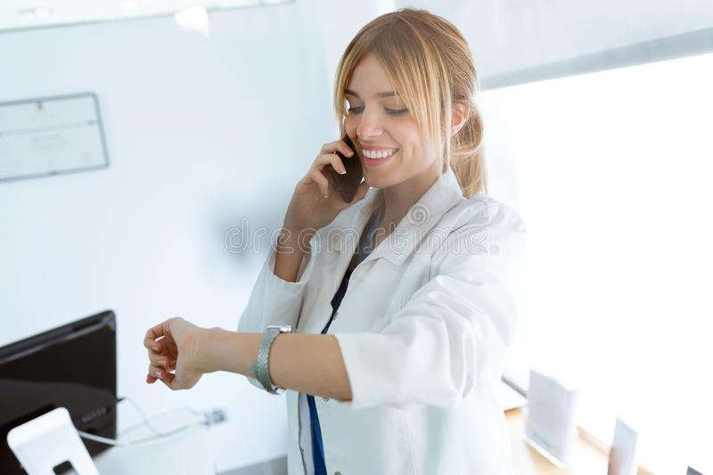 Attractive female doctor talking with her mobile phone while watching her watch in medical consultation. Shot of attractive female doctor talking with her mobile stock images