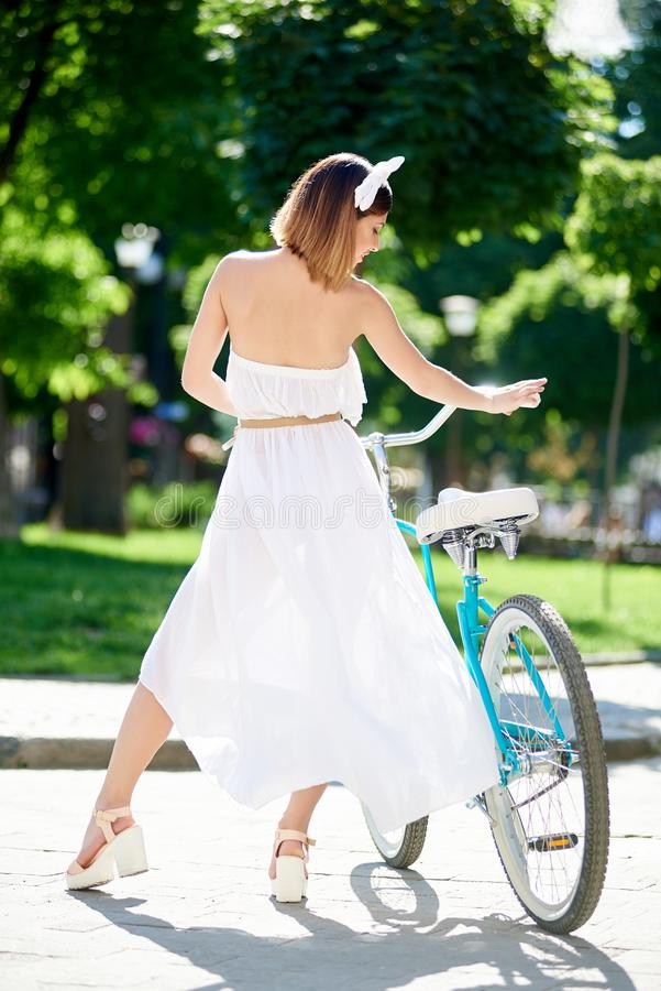 Pretty girl posing from the back near blue bicycle royalty free stock images