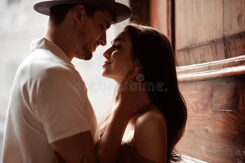 Shot of beautiful female and male in hat, going to kiss each other, express great love and real mutual relationships royalty free stock image