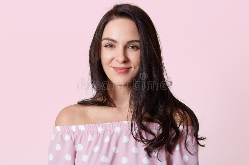 Shot of beautiful smiling woman with clean skin, natural make up, long brunette hair posing with naked shoulders, wearing pink stock photography