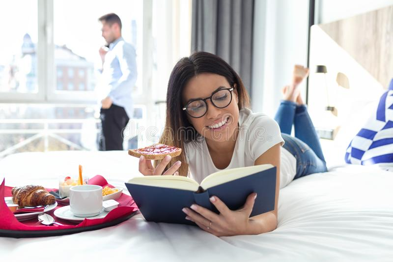 Beautiful smiling woman reading a book and having breakfast while lying on bed in hotel room royalty free stock images