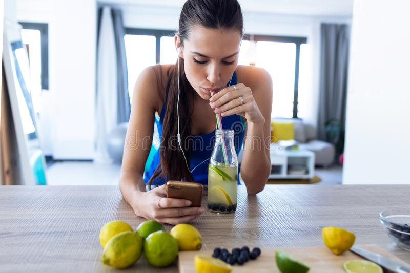 Beautiful sporty young woman drinking detox juice while listening to music with smartphone in the kitchen stock image