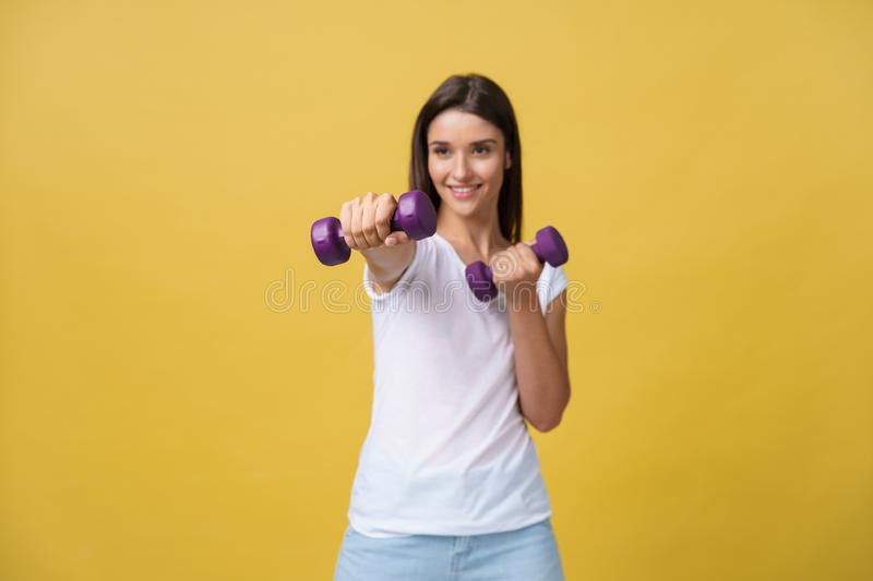Shot of a beautiful and sporty young woman lifting up weights against yellow background. royalty free stock photography