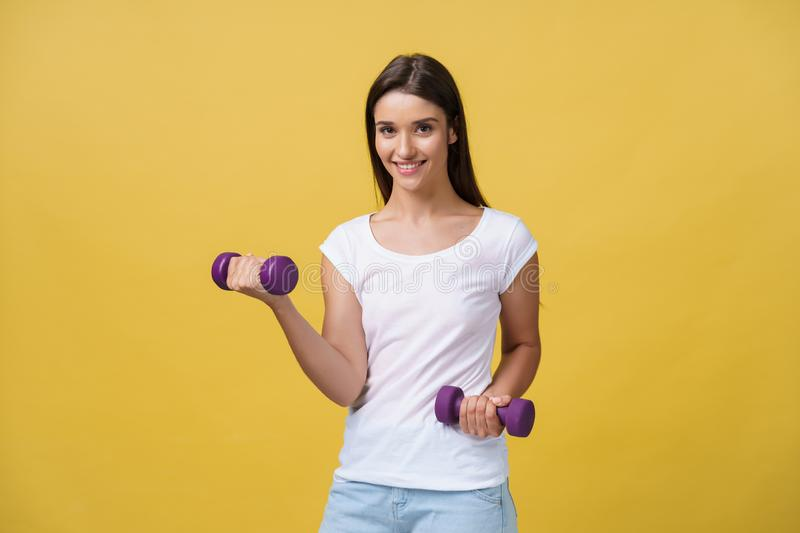 Shot of a beautiful and sporty young woman lifting up weights against yellow background. stock photography
