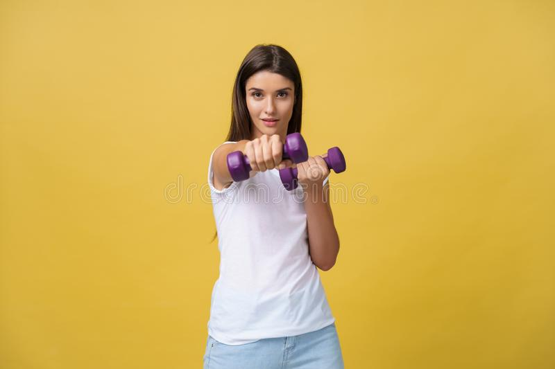 Shot of a beautiful and sporty young woman lifting up weights against yellow background. royalty free stock image