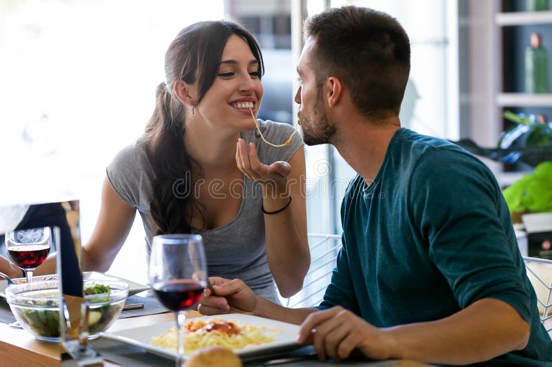Beautiful young couple sharing single spaghetti getting closer to kissing in the kitchen at home royalty free stock photography