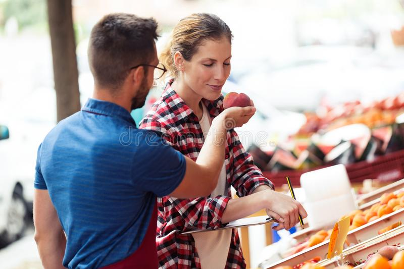Beautiful young customer smelling nectarina in health grocery shop. royalty free stock photos