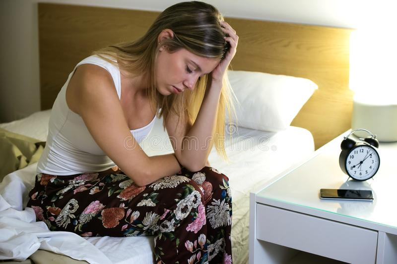 Beautiful young exhausted woman suffering insomnia sitting on bed in the bedroom at home. royalty free stock image
