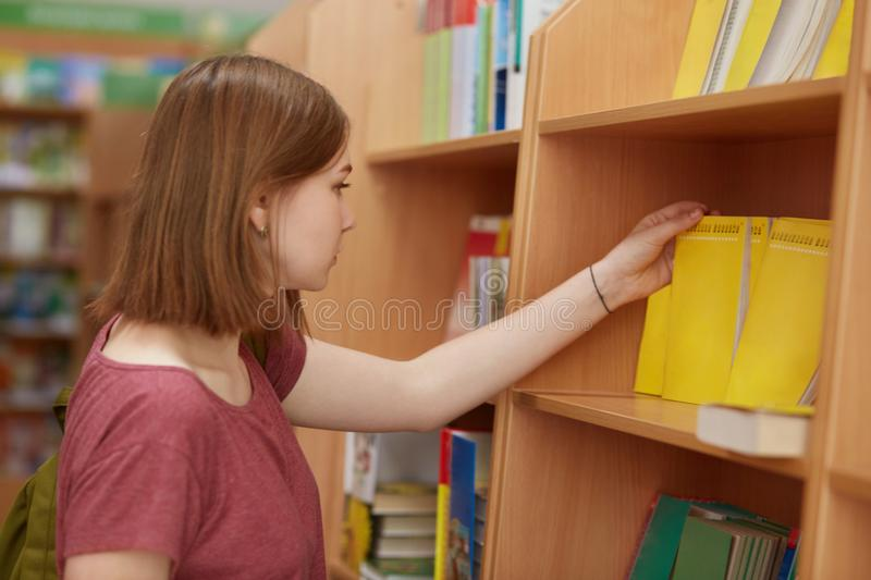 Shot of beautiful young female student stands at college library, chooses book to read, likes study, carries rucksack, dressed in royalty free stock photos