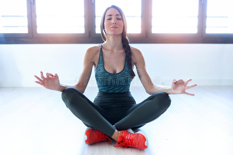 Beautiful young woman doing yoga and relaxing at home stock image