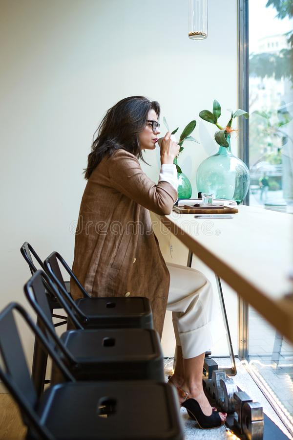 Beautiful young woman drinking Matcha green tea latte on wodden table in the coffee shop. royalty free stock photography