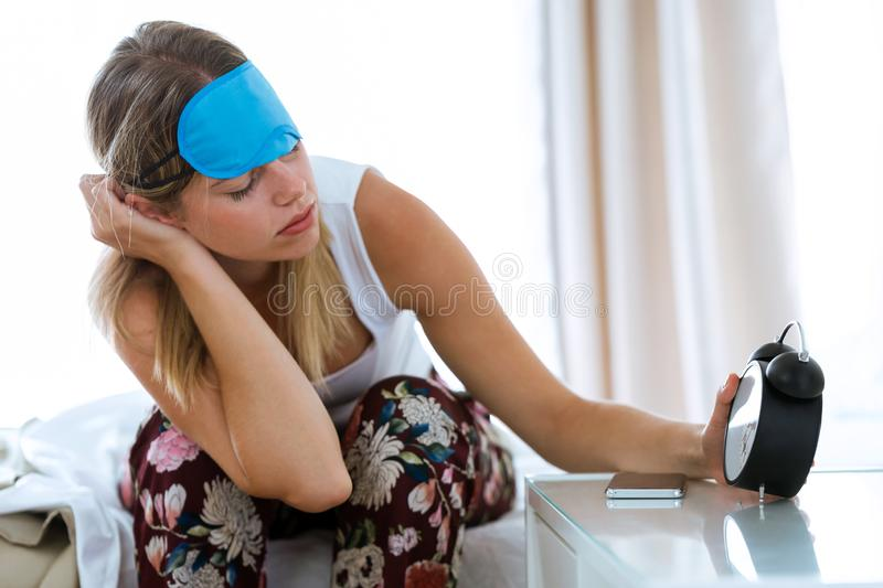 Beautiful young woman sitting on bed with sleep mask trying to wake up with alarm clock in bedroom at home. royalty free stock photo