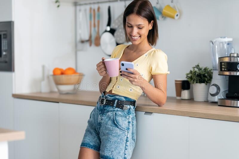 Beautiful young woman using her mobile phone while drinking a cup of coffee in the kitchen at home royalty free stock images