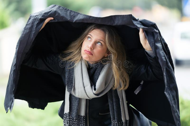 Beautiful young worried woman covering herself with her jacket because it`s raining in the street. Shot of beautiful young worried woman covering herself with stock image