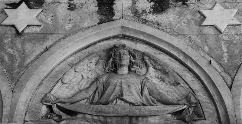 Angel figure with two stars. Shot in black and white detail of the sculpture on the facade of this historic building cemetery representing some characters / royalty free stock photography