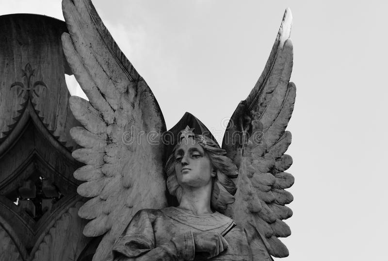Elegant angel next to the cross. Shot in black and white detail of the sculpture on the facade of this historic building representing some characters / animals royalty free stock photo