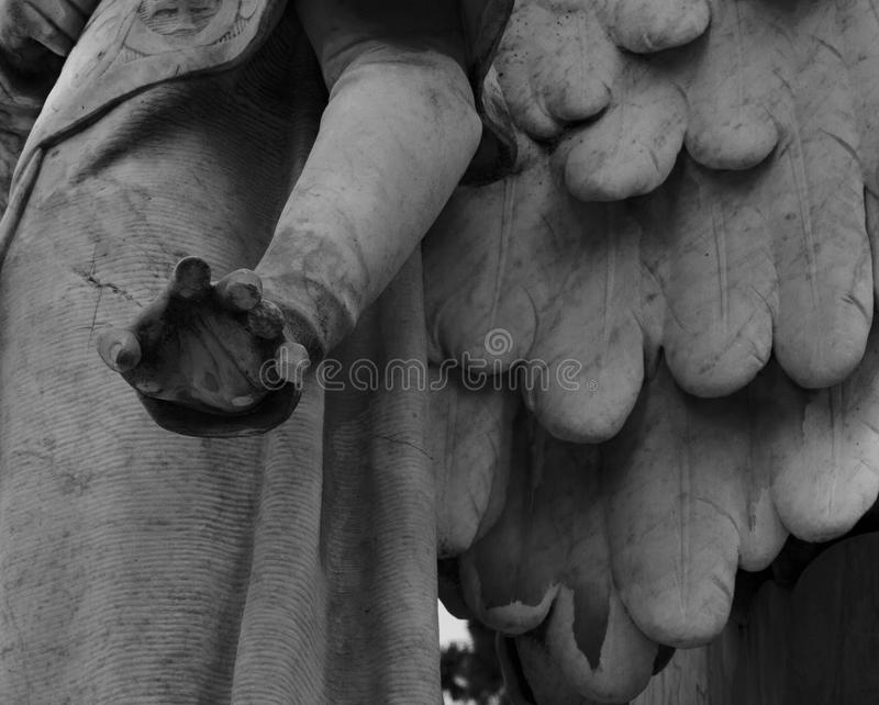 Broken fingers on the angel´s hand. Shot in black and white detail of the sculpture on the facade of this historic building representing some characters / stock photos