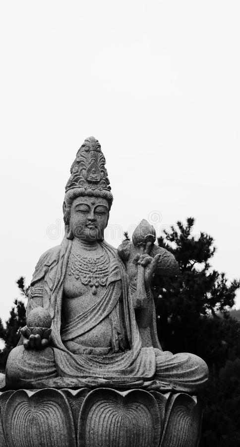 Buddha statue. Shot in black and white. Detail on the sculpture representing an image of buddha,on the main garden, on the island of Miyajima. Set in Hiroshima stock photo
