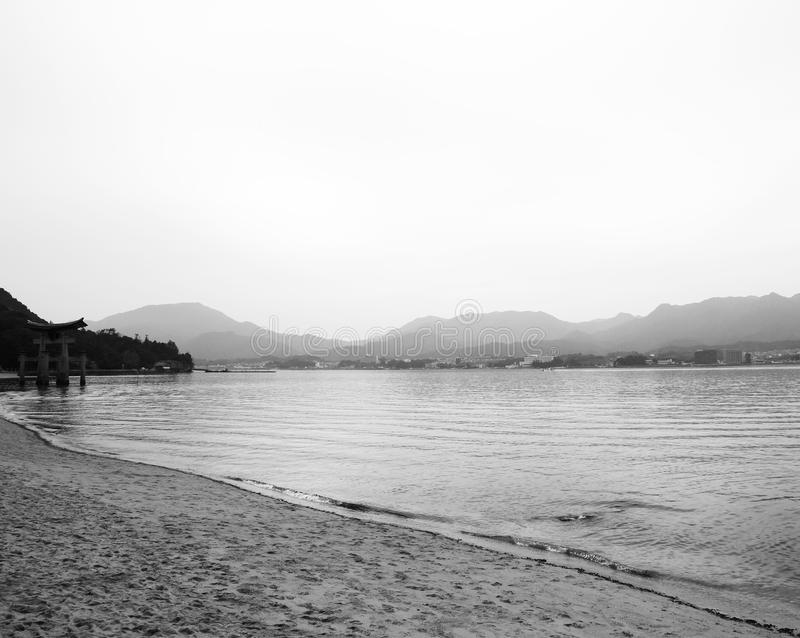 A distant view. Shot in black and white. Detail on the simbolic tori on the sea close to the island of Miyajima. Set in Hiroshima, Japan, Asia stock images