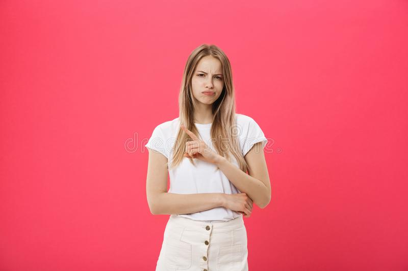 Shot of bored annoyed beautiful teenage girl with straight blond hair looking at camera with boring and annoying face. Wearing trendy eyewear and long-sleeved royalty free stock photo
