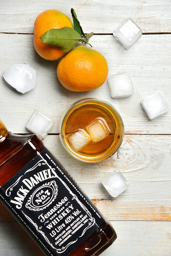 A shot and a bottle of whiskey on wooden table surrounded by ice cubes and tangerines royalty free stock photos